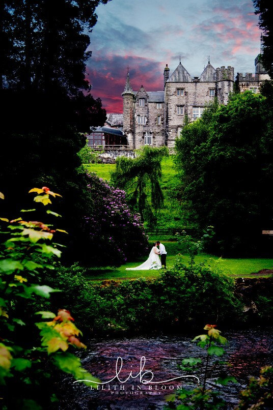 Bridal Couple in Lower Gardens at Craig y Nos Castle viewd from across the river