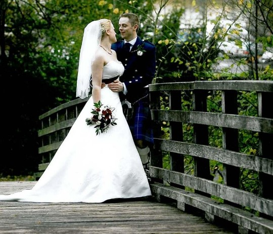 Couple on wooden footbridge leading from lower garden to country park