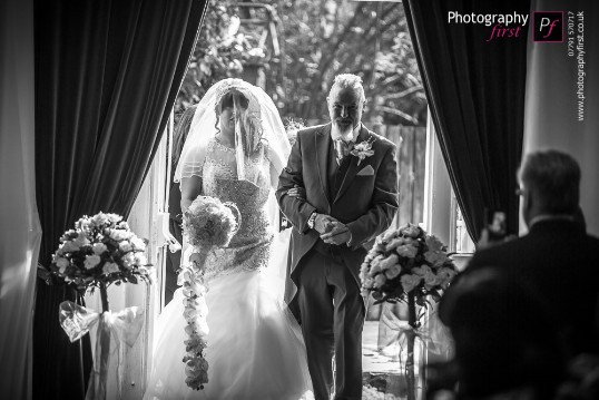 Bride and father entering ceremony room from the courtyard