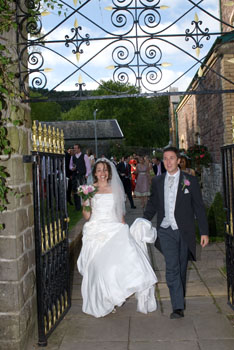 Bride and Groom walk through gate from theatre gardens at Craig y Nos Castle Wedding Venue in Wales