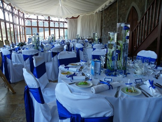 Craig y Nos Castle Swansea the Conservatory tables laid up with Blue and white chair covers and blue flowers