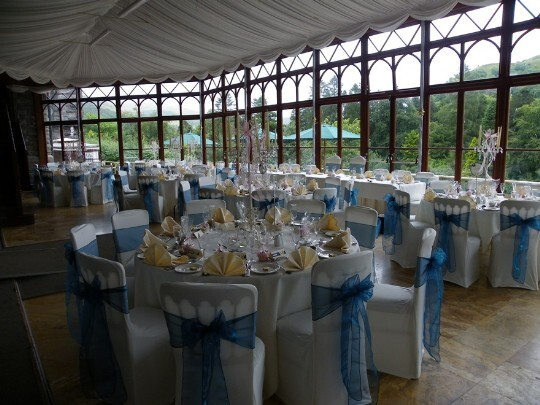 Craig y Nos Castle Wedding Venue Conservatory blue ribbons on white chair covers