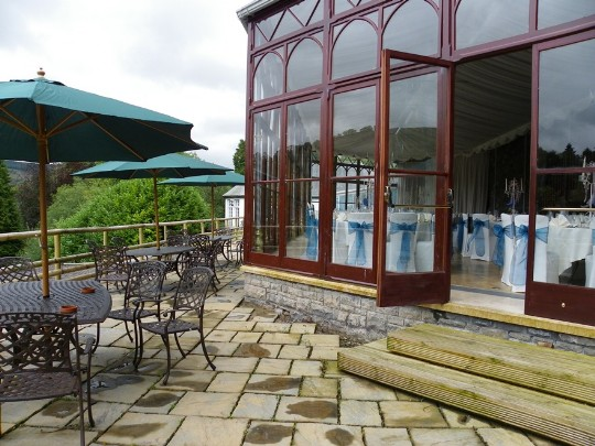 Craig y Nos Castle Wedding Venue in Swansea showing the Conservatory terraces and wrought iron tables