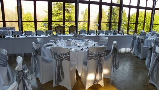 Craig y Nos Castle Wedding Venue Wedding Breakfast tables set up with silver sashes on whilte chair covers