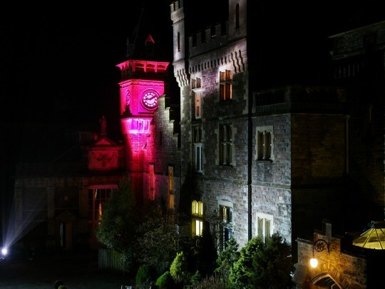 Craig y Nos Castle Wedding Venue Swansea Floodlit at Night in grey and purple alternating colours