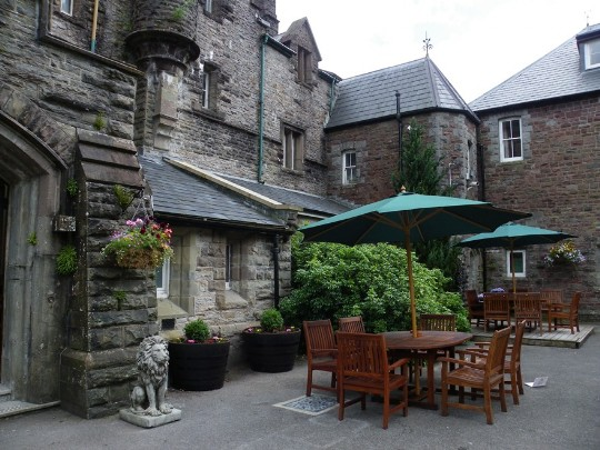 Craig y Nos Castle Wedding Venue Front Courtyard teak garden seats and tables with green canopies