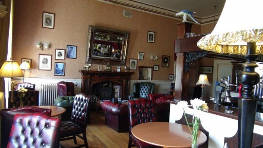Craig y Nos Castle Patti Bar leather chesterfield sofas, Edwardian fireplace, wall with pictures of Adelina Patti
