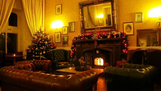 Craig y Nos Castle Patti Bar with roaring log fire, Christmas tree in corner, chesterfield sofas around fire
