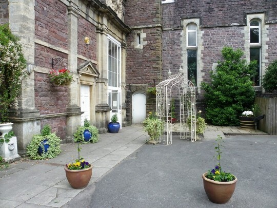 Hanging baskets and the floral white metal arch outside the Craig y Nos Castle theatre / ceremony room