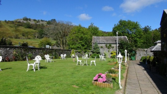 The lawned theatre gardens white tables and chairs. Craig y Nos Castle in South Wales