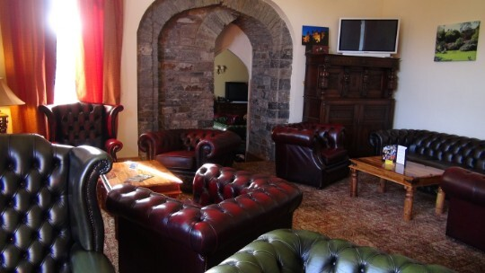 Craig y Nos Castle Wedding Venue Reception Lounge with leather chesterfield sofas and chairs