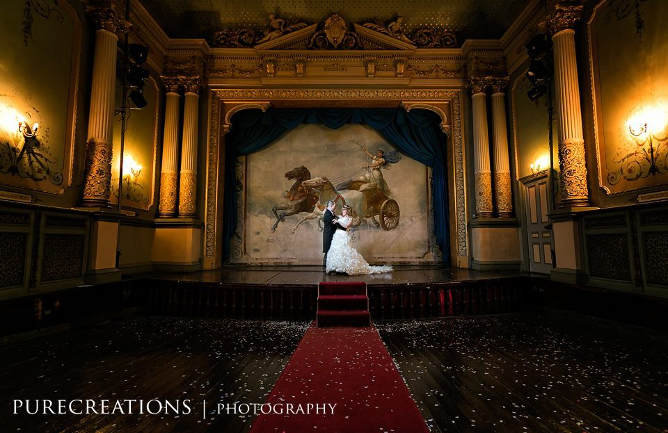 Confetti and Bride and Groom on the stage at Craig y Nos Castle's Opera House by Pure Creations Wedding Photography