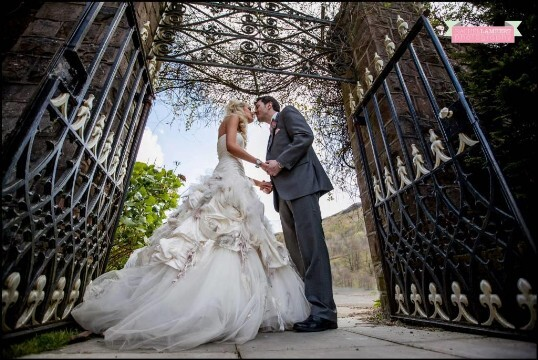Wedding Couple by wrought iron gate entrance to theatre gardens by Rachel Lambert Photography